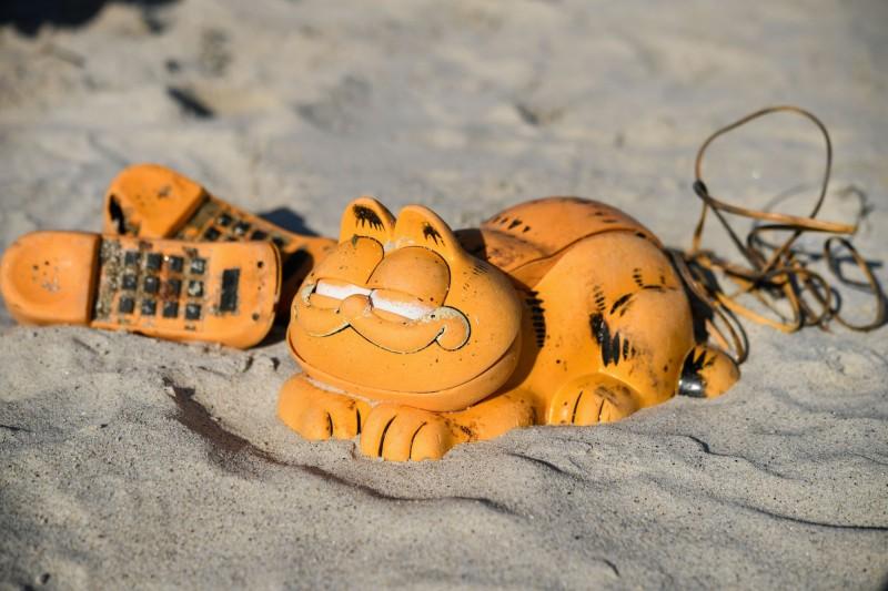 自1980年代以來,法國布列塔尼的海岸總是會有加菲貓造型的橙色電話座機沖到海灘上,而加菲貓從何而來的謎團從20世紀延續到21世紀,如今終於解開。(法新社)