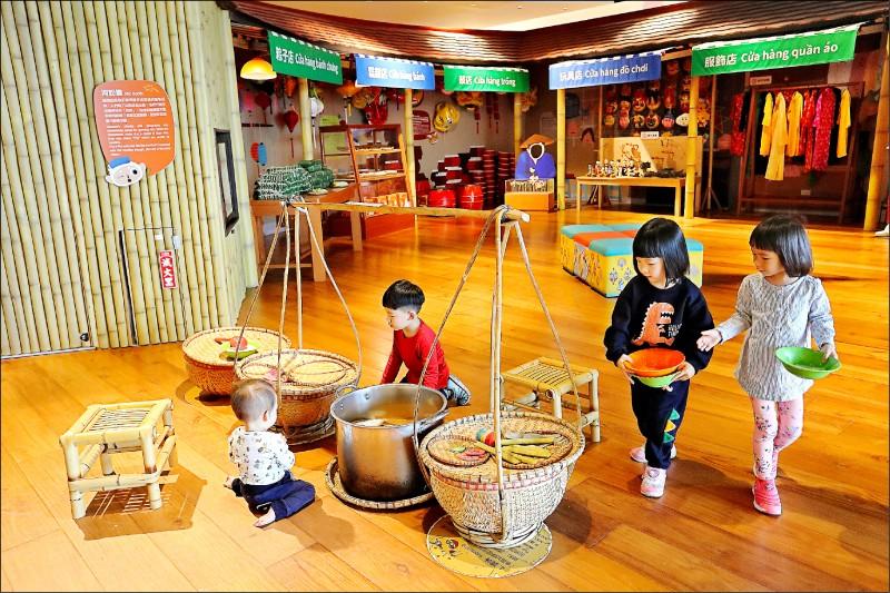 坐在竹擔攤前扮演河粉攤老闆與顧客,讓孩童透過扮家家酒認識越南食的文化。(記者李惠洲/攝影)