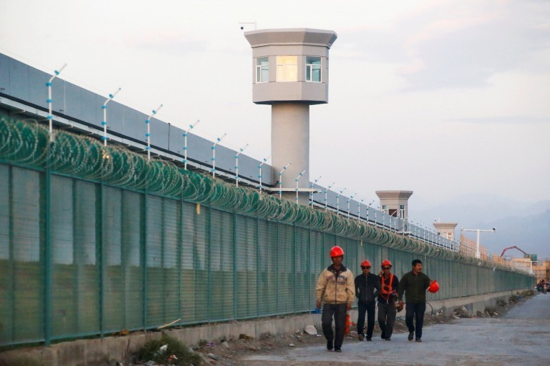 中國政府在新疆地區建立名為「職業培訓中心」的「再教育營」,以關押維吾爾人等少數民族;中國不僅對新疆維族人嚴厲控管,對控管這些維族人的漢族公務人員也施以巨大壓力。圖為新疆的工人走在中國政府所謂的「職業培訓中心」的圍牆旁。(路透檔案照)