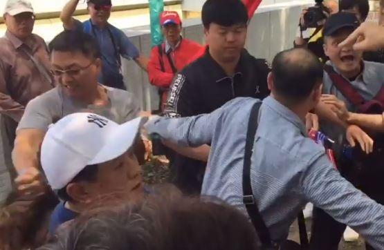 灰衣男子在抗爭現場揮拳攻擊大學生的頭部。(圖取自臉書)