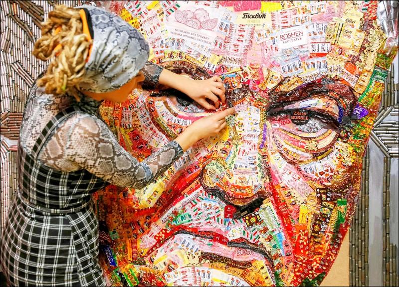 烏克蘭藝術家馬欽科(左)27日在基輔用總統波洛申科創立的烏國「如勝」糖果集團20多公斤糖果的包裝紙及彈殼,拼貼創作波洛申科的肖像,並命名為「貪腐之臉」。(路透)