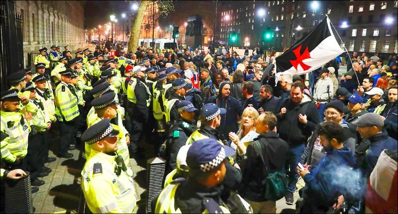 英國首相梅伊的脫歐協議二十九日再度遭到國會否決,大批挺歐派人士當晚聚集在首相官邸前,與負責維安的員警對峙。(法新社)