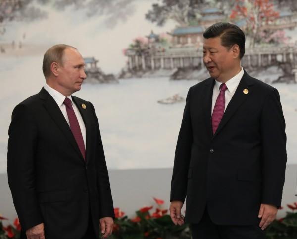俄方新實施網路監管法規,但否認會向中國一樣築起網路長城。圖為俄國總統普廷(左)與中國國家主席習近平(右)。(歐新社)