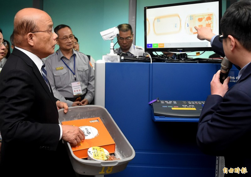 行政院長蘇貞(左)2日上午再度視察桃園機場非洲豬瘟檢疫作業,並向X光機安檢人員詢問如何判讀顯像內容。(記者朱沛雄攝)