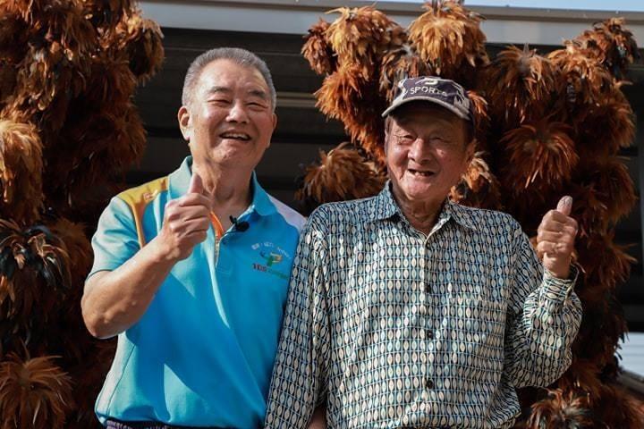 溪口踢毽運動推手蔡伯期(左)與手工雞毛撣子職人陳忠露相見歡。(黃孝文提供)