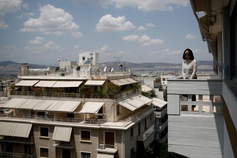 大批中國人透過在希臘投資房產,順利取得希臘「黃金簽證」。圖為一名潛在的中國投資客,正在雅典市尋覓屬意的公寓。(路透檔案照)