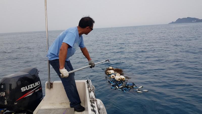 蔡馥嚀一行人發現望海巷保育區海面上飄著1張3層流刺網,下方還掛上鉛石增加重量,費了一番力氣才將漁網撈起。(記者林欣漢翻攝)