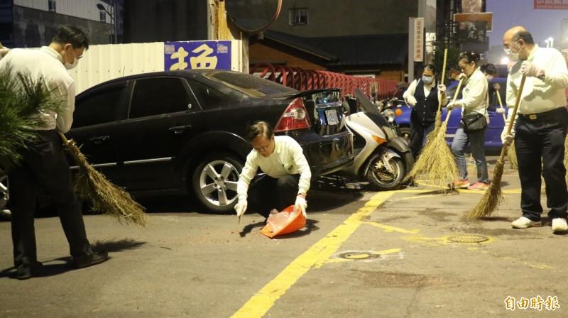 大甲媽起駕遶留下滿地垃圾,台中慈濟醫院院長簡守信蹲在地上,以畚箕清掃撿拾垃圾。(記者歐素美攝)