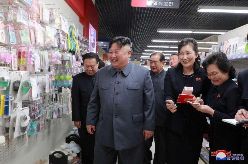 金正恩不僅在參觀服裝部門時拿起男鞋仔細端詳,在視察所有樓層也掛著滿意的微笑。(路透)