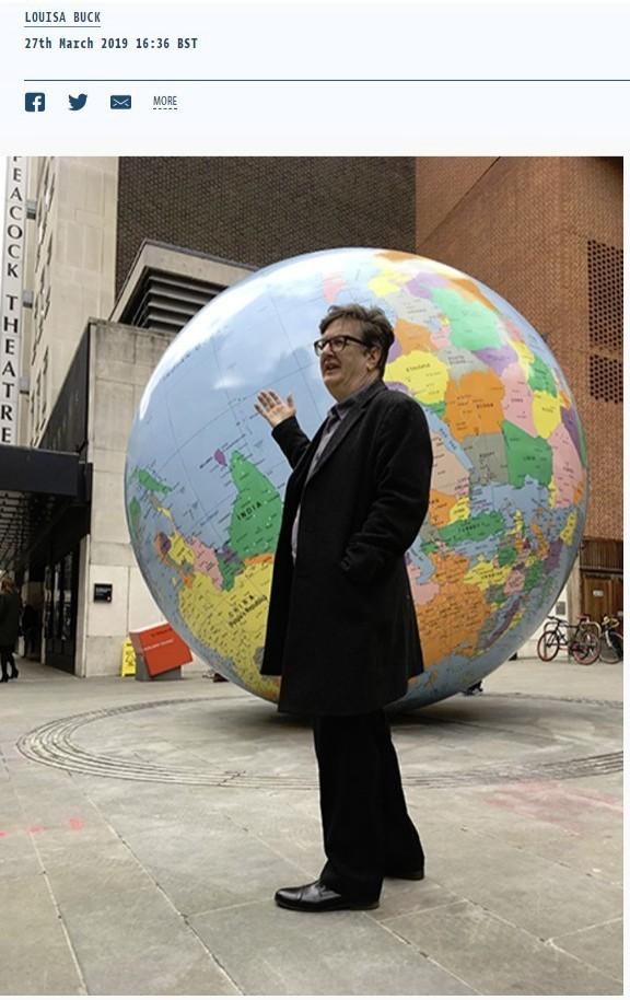 藝術家華林格站在作品《顛倒世界》前。(擷取自《藝術家報》)