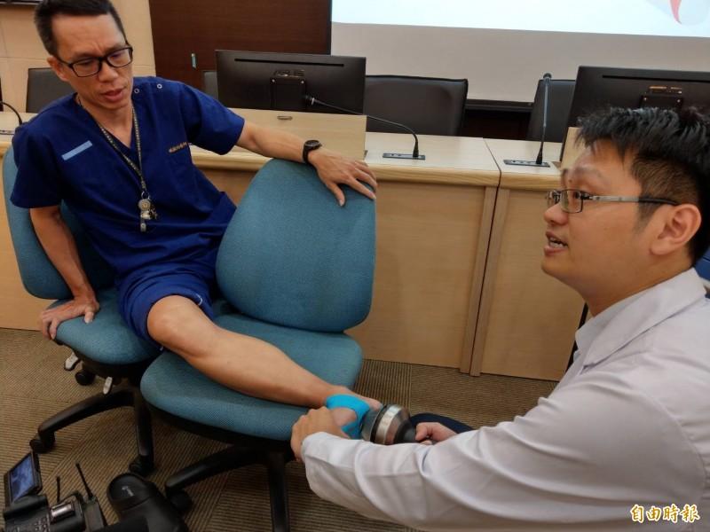 醫師蘇烱輝(右)示範利用體外震波為足底筋膜炎患者治療。(記者方志賢攝)