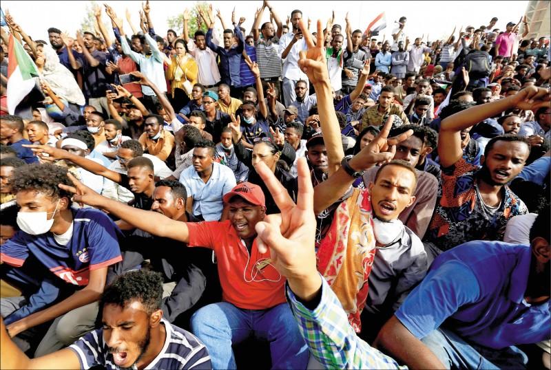 蘇丹總統巴席爾垮台,在國防部外抗議的民眾十一日歡欣鼓舞。(路透)