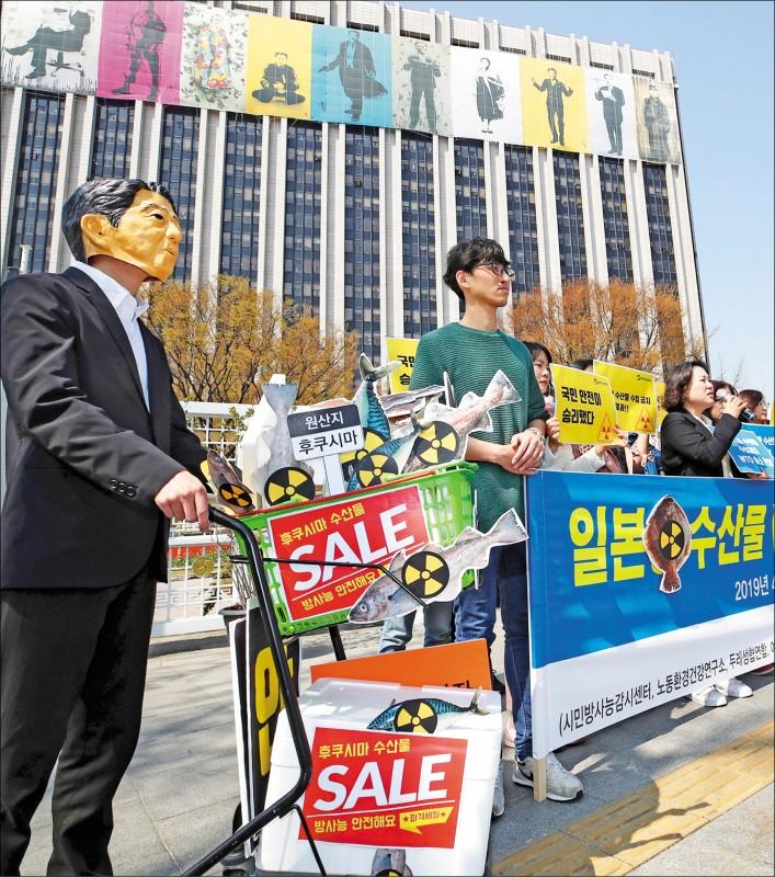 世貿組織(WTO)爭端解決機構十一日做出終審裁決,認為南韓禁止日本福島等八縣水產品進口,並未違反相關國際經貿法規。圖為南韓公民團體十二日在首爾的中央政府聯合辦公大樓前,表達對WTO裁決的支持。(歐新社)