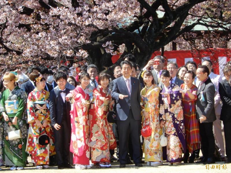 日本首相安倍晉三今天在新宿御苑舉辦平成最後一次賞櫻會,人氣女子偶像團體「桃色幸運草Z」拉著他一起比招牌手勢。(記者林翠儀攝)