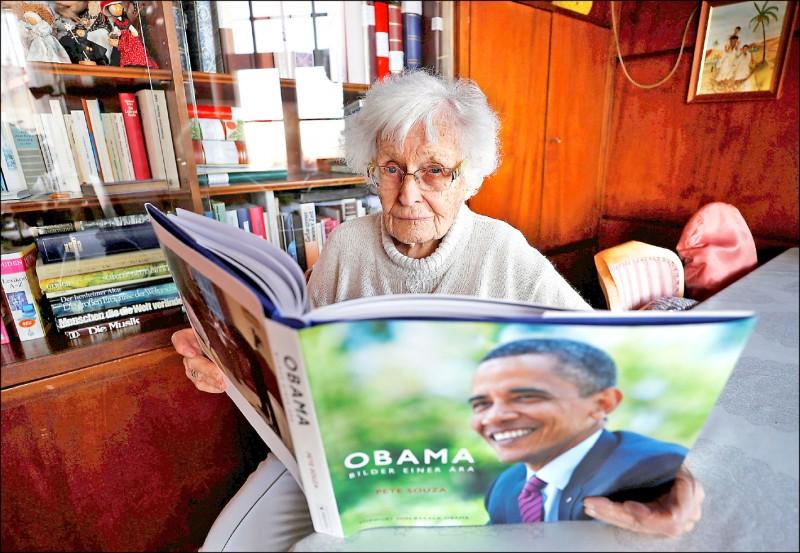 圖為百歲人瑞阿嬤海瑟在家中接受媒體訪問時,閱讀一本以美國前總統歐巴馬為主題的攝影文集。(路透)