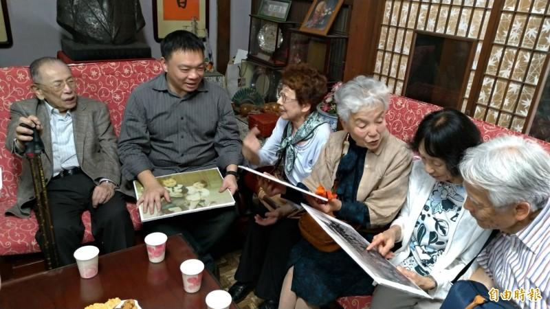 日人住吉秀松的次子住吉弘光(左一)與家族成員(右側坐者)在昔日台南住吉老家看著老照片回憶過往歲月生活點滴。(記者王俊忠攝)