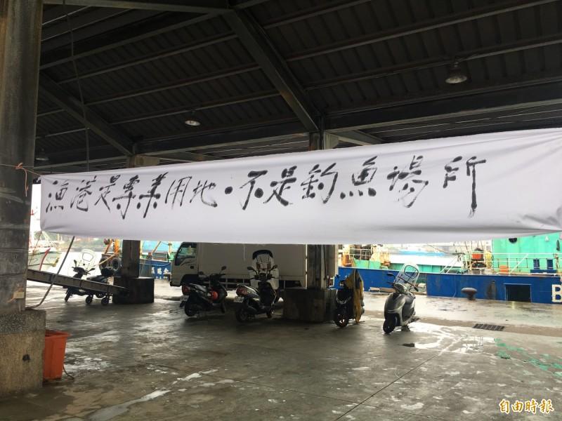 漁民在正濱漁港懸掛「漁港不是釣魚場所」等布條反對開放漁港垂釣。(記者林欣漢攝)