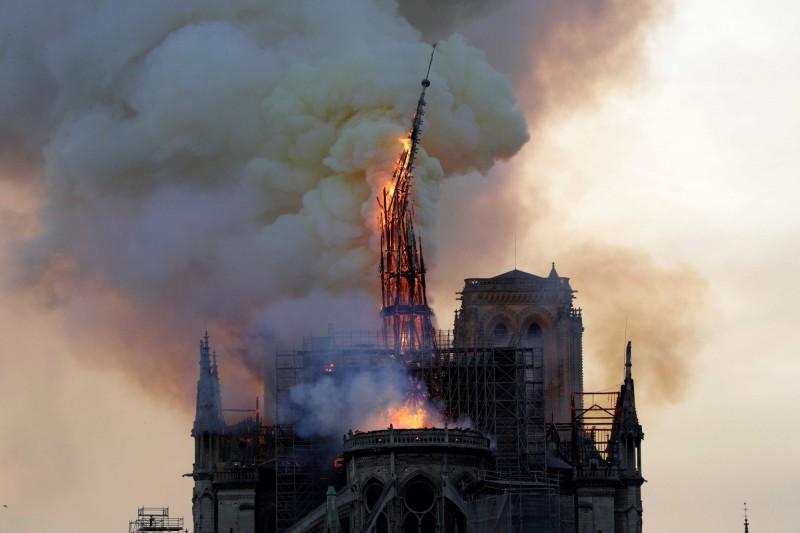 巴黎聖母院的尖塔不敵大火,在眾目睽睽之下傾倒毀壞。(法新社)