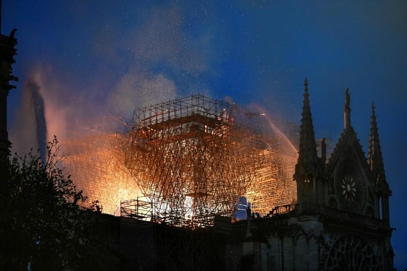 法國巴黎聖母院於當地時間15日傍晚發生大火,當局雖緊急動員救災,教堂屋頂仍被大火燒毀崩落。(法新社)