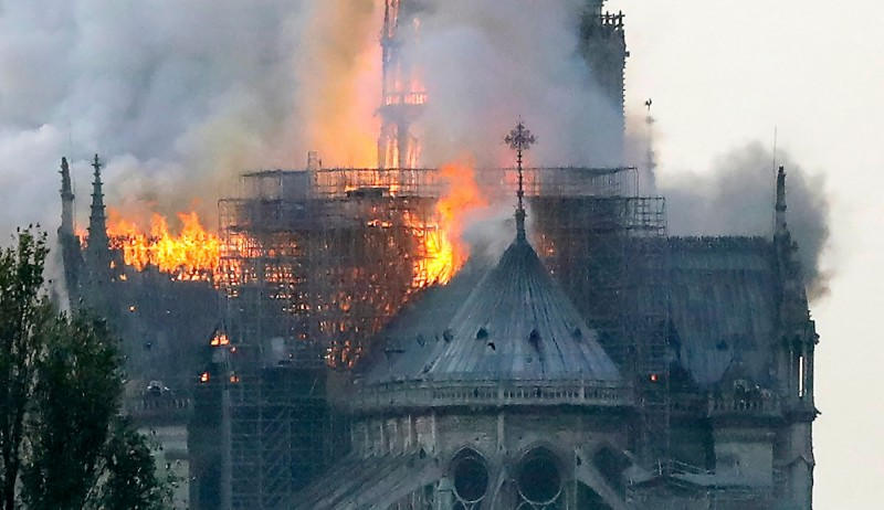 巴黎聖母院的尖塔被大火所包圍。(法新社)