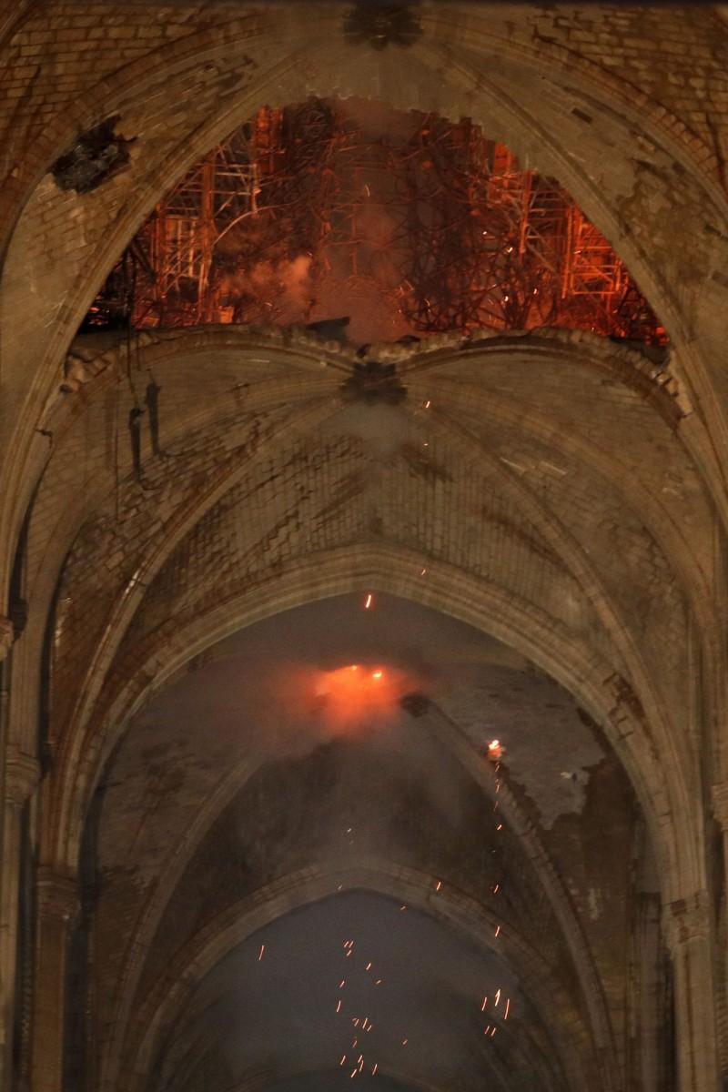 法國巴黎聖母院於當地時間15日傍晚發生重大火警,屋頂的火花不斷掉落教堂大廳。(路透)