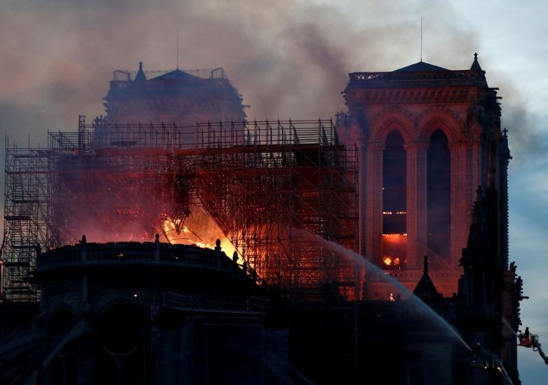 消防人員搭雲梯從高處灑水,想撲滅從聖母院屋頂不斷冒出的熊熊烈火。(路透)