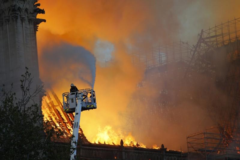 在聖母院外圍有許多消防員不斷拉水線噴水搶救,也有部分消防人員是搭雲梯從高處灑水,想撲滅從屋頂不斷冒出的熊熊烈火。(美聯社)