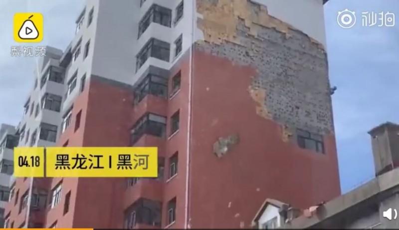 中國黑一處高樓的外牆皮,在經歷一陣強風後,竟整片掀起從高空墜落。(圖擷取自梨視頻)