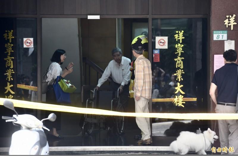 81號大樓主委(格子襯衫)認為,住在危樓隔壁,有如中國在台灣隔壁一樣害怕。(記者黃耀徵攝)