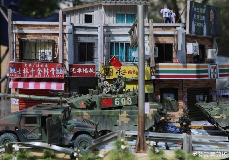北京模型賽這件作品引起話題,中國解放軍坦克耀武揚威輾過台北街頭,街景相當逼真,中國網友拍攝的照片右上角可清楚看見,超商頂樓廣告看板有蔡英文總統照片,和「民主建國,點亮台灣,2020」字樣,顯然是想像中蔡英文競選連任的廣告看板。(圖擷取自「世界特種部隊與軍武資料庫」臉書粉專)