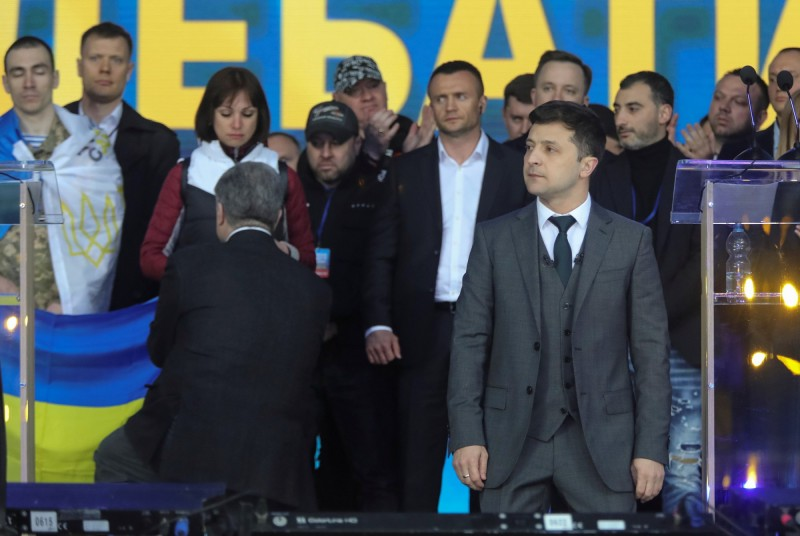澤倫斯基(右)與波洛申科(左)兩人辯論到一半,紛紛向大眾下跪。(路透)