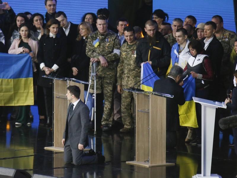 澤倫斯基(左)稱要為頓巴斯衝突中喪生的罹難者家屬下跪,波洛申科(右)見狀也立刻單膝跪地,不過他背對著觀眾,親吻支持者手裡的國旗。(美聯社)