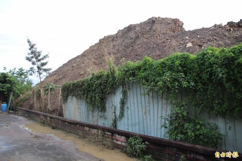 釀禍的土石方堆置場,暴雨後過高的土壓把鐵皮圍籬都壓垮。(記者黃美珠攝)