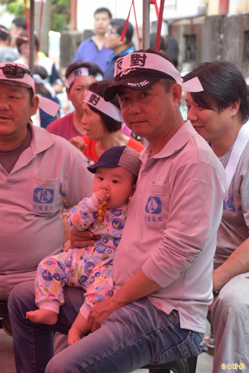 一名男子帶著幼兒參加旗山生命紀念園區說明會,表達反對設置立場。(記者蘇福男攝)