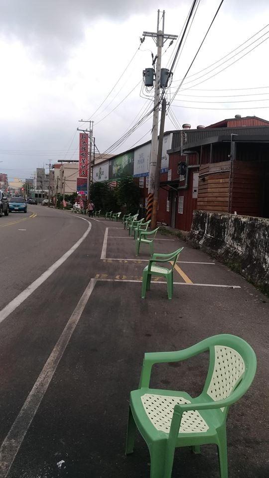 頭份市一家餐廳為替客人留車位,竟異想天開用塑膠椅霸佔路邊車格,引發網友痛批。(記者鄭名翔翻攝)