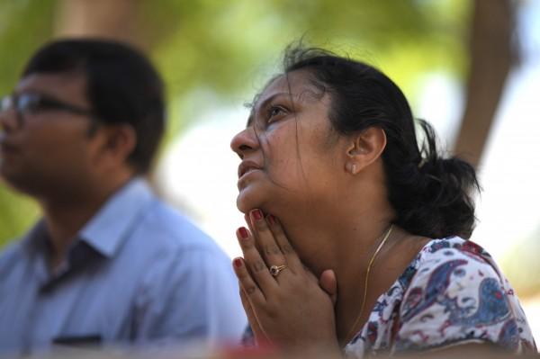 一名婦人在聖塞巴斯提安教堂外流淚祈禱。(法新社)