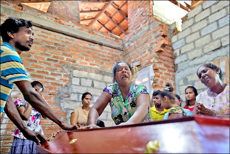 斯國二十一日復活節連環爆炸案的罹難者家屬,圍著年僅十二歲的死者棺木放聲大哭。(美聯社)