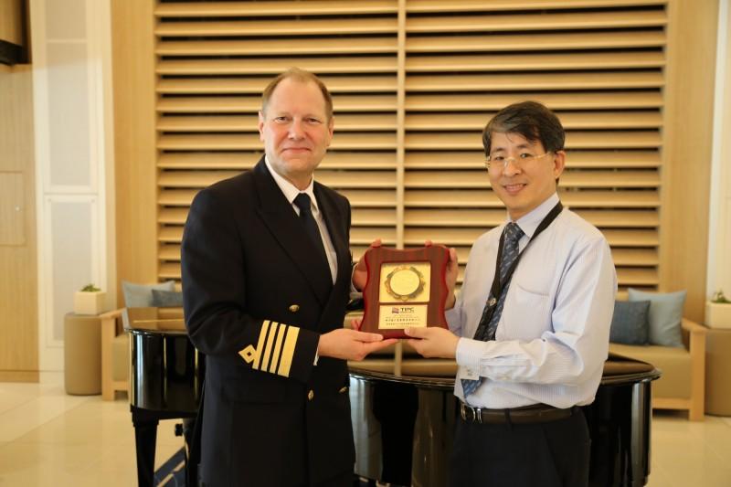獵戶星號首次靠泊基隆港,基隆港務分公司棧埠事業處長曹至宏(右)致贈首航紀念牌。(基隆港務分公司提供)