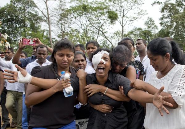 連環爆炸案受害者家屬(中),在其丈夫、兩名孩子、三位兄弟姊妹下葬時放聲大哭。(美聯社)