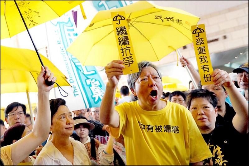 香港泛民主派前立法會議員李卓人,24日在法院外號召民眾手持黃傘及標語聲援「佔中9子」。(路透)