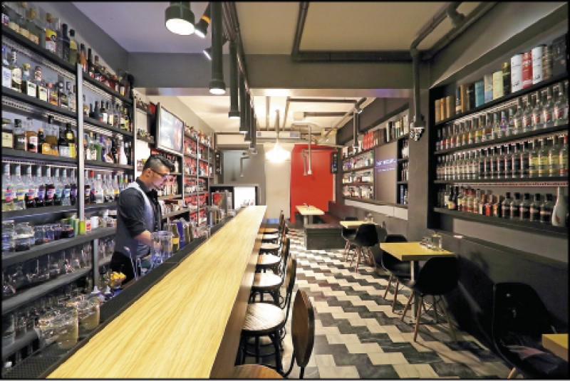 吧檯上方一字排開的水管燈和燈泡串,點出「馬賽克酒吧」的工業風格。(記者李惠洲/攝影)