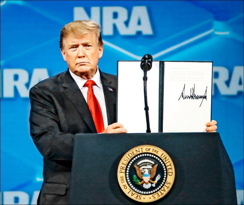 川普廿六日在美國全國步槍協會年度大會上,展示他簽署退出聯合國武器貿易條約的文件。(歐新社)