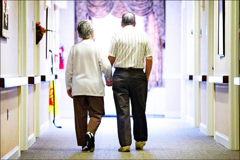 「要活就要動!」即使是散步等簡單的肢體活動,都有助中、老年人保持活動力。圖為一對老夫妻牽手在走廊上散步。(美聯社檔案照)