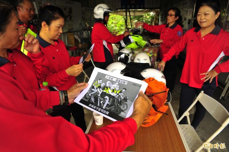 公親里巡守隊看到KUSO插畫,因為成員多數年紀大,比較不會用手機,把插畫印出來給成員分享。(記者王捷攝)