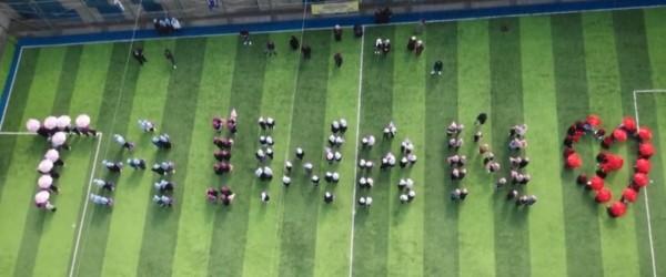 敘利亞孩童以陽傘拼出「TAIWAN」字母與愛心圖樣。(擷取自臉書影片)