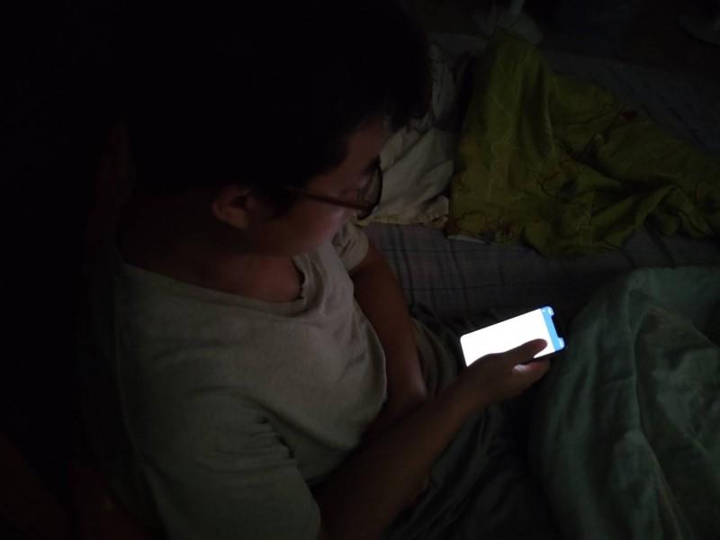 夜間使用手機,由於手機的藍光會抑制褪黑激素分泌,因此影響睡眠品質。(記者王捷翻攝)