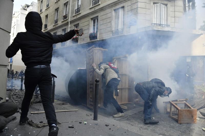 大批群眾於1日國際勞動節當天走上法國巴黎街頭遊行,部分激進份子在遊行開始不久後,就朝警方丟擲瓶罐與人行道脫落的石塊,以及破壞路邊車輛。(歐新社)
