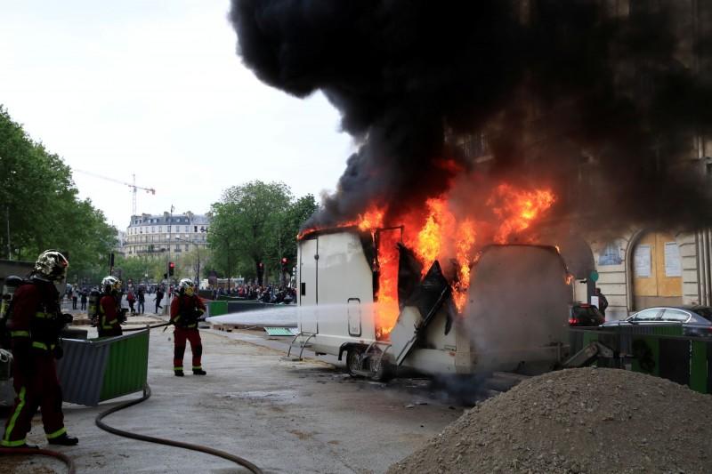 有激進份子破壞路邊車輛,消防人員進行處理。(路透)