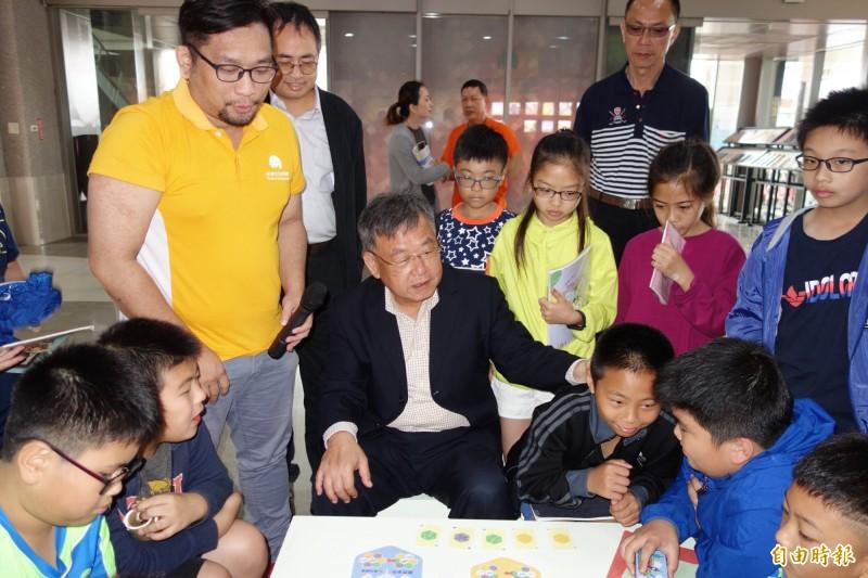 賴峰偉與文澳國小學生切磋桌遊遊戲。(記者劉禹慶攝)