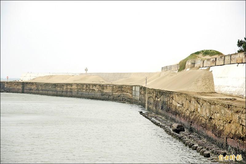 外埔漁港長年受飄沙侵襲,北邊堤防堆出一半層樓高的沙丘。(記者鄭名翔攝)
